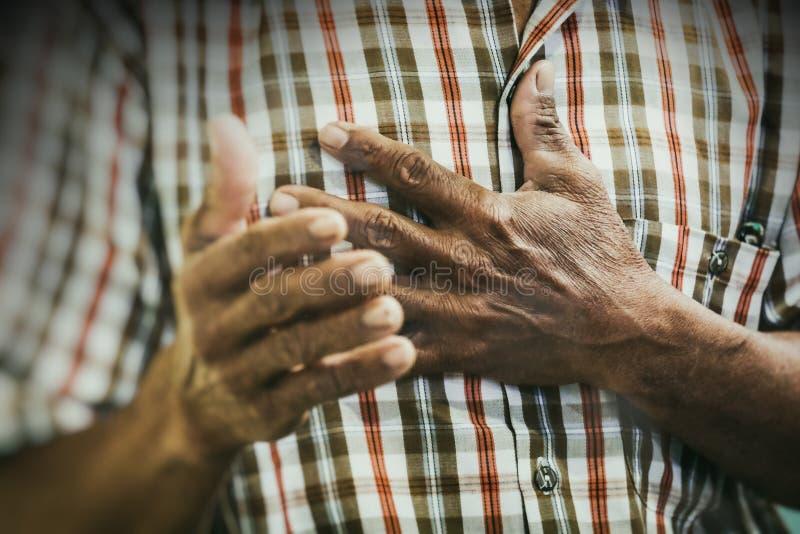 Gammal asiatisk man som ber till Jesus Christ med hans hand på hjärta i bönmötet royaltyfria bilder
