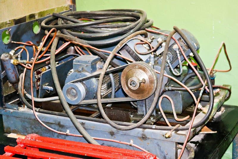 Gammal asynkron elektrisk motor med rör och slangar, drivande för bälte i en industrianläggning royaltyfria bilder