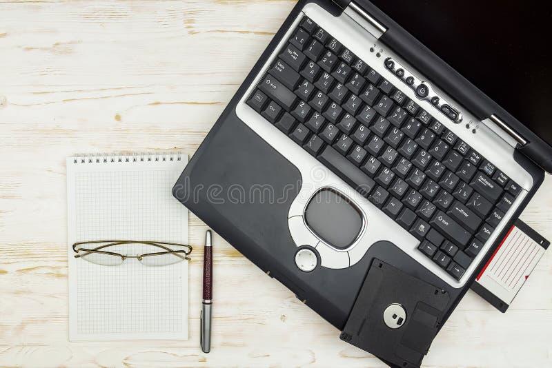 Gammal bärbar dator med disketter, en anteckningsbok, exponeringsglas och en penna på a royaltyfri fotografi