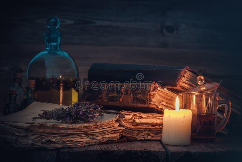 Gammal böcker och stearinljus, tinktur- eller dryckflaska, exponeringsglas av drycken och grupp av torra sunda örter royaltyfria foton