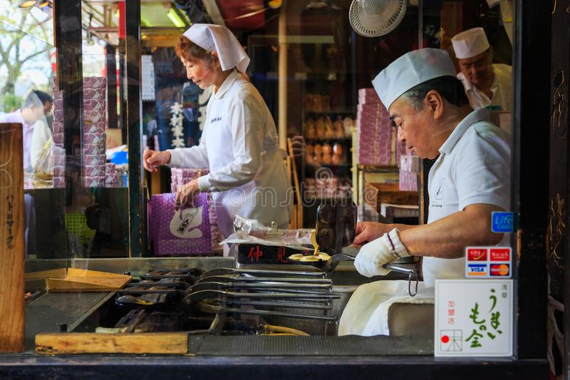 Gammal bageriman som gör berömt mellanmål av Nakamise Dori det shoppa området av den Sensoji templet den berömda templet i Tokyo, royaltyfri bild