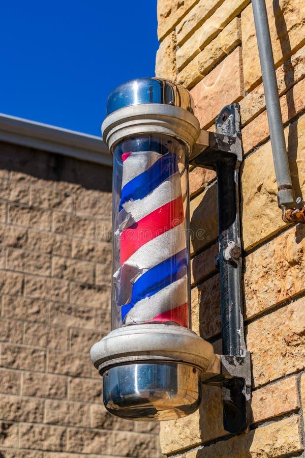 Gammal barberarskylt på sidan av en Barber Shop royaltyfri bild