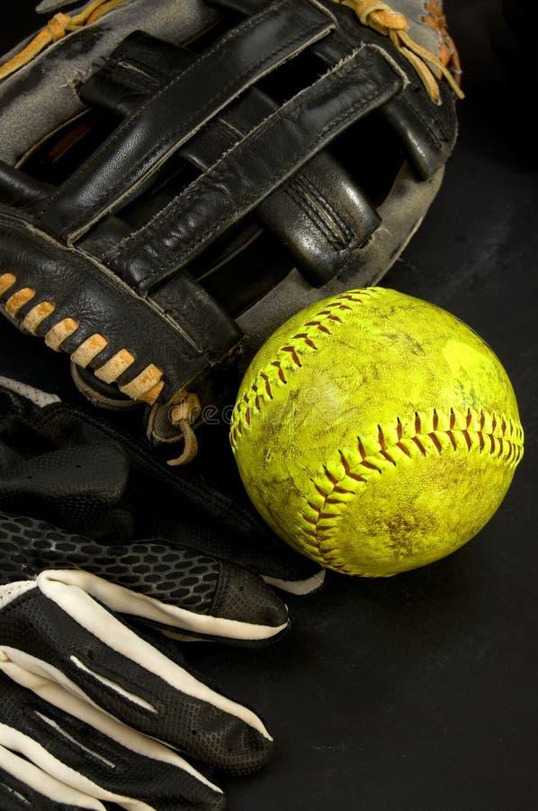 Gammal baseballhandske med gula softball- och smethandskar royaltyfria foton