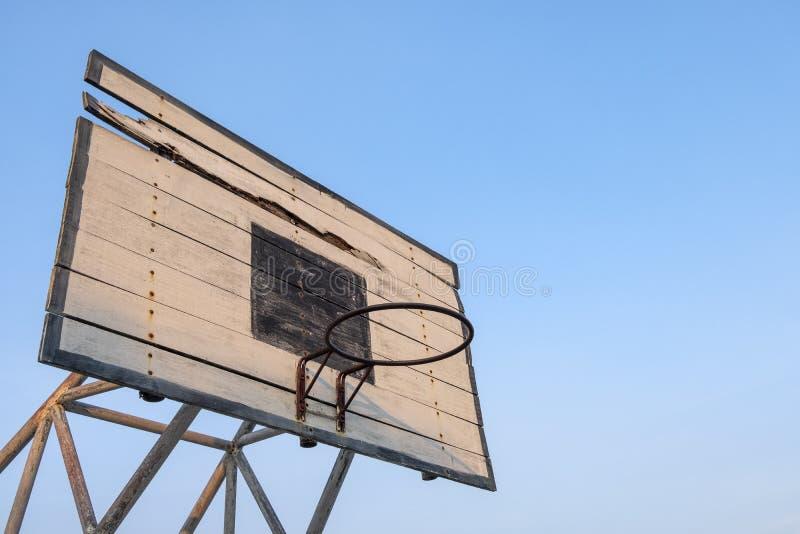 Gammal basketmålbräda, basketbeslag med bakgrund för blå himmel arkivfoto
