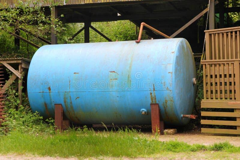 Gammal behållare för blåttmetallgårdsplan arkivfoto