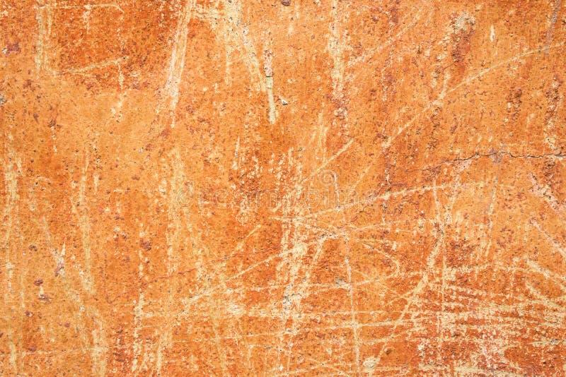 Gammal bekymrad skrapad kanstött ockraterrakotta Rusty Background med den Grungy texturväggen Nedfläckad cement- eller stenytters royaltyfri bild