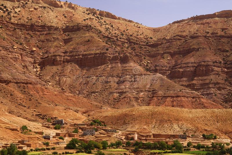 Gammal berberbyoas med husbyggande av lerategelstenar framme av den mäktiga höga ojämna röda bergframsidan, Klyfta du Dades, arkivbild
