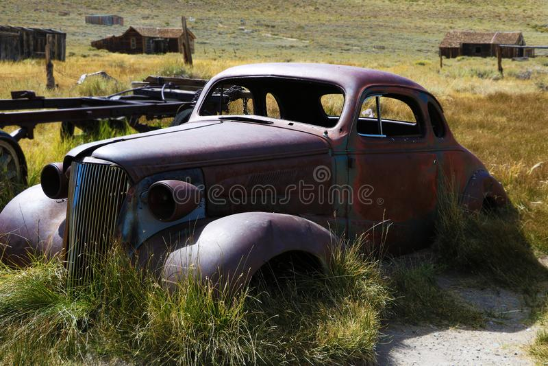 Gammal bil: gammal bil som är rostig, i ett fält, i en historisk spökstad, Bodie royaltyfria foton