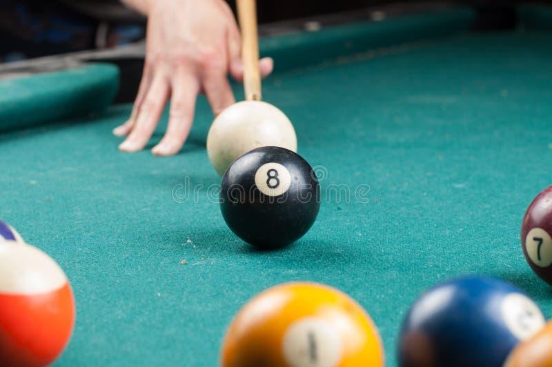 Gammal billiardboll 8 och pinne på en grön tabell billiardbollar som isoleras på en grön bakgrund arkivfoto