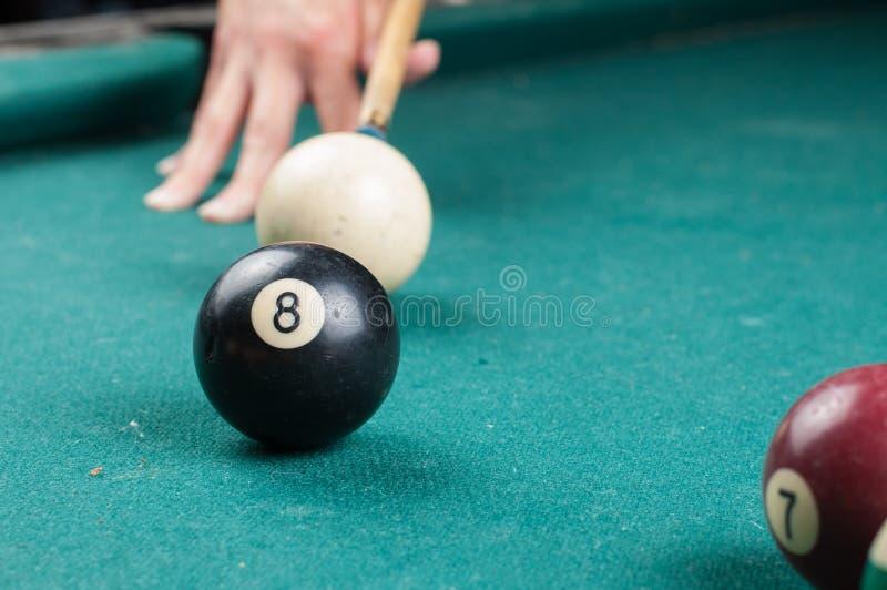 Gammal billiardboll 8 och pinne på en grön tabell billiardbollar som isoleras på en grön bakgrund arkivbilder