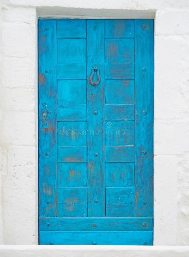 Gammal blå dörr på den vita stenväggen arkivbild