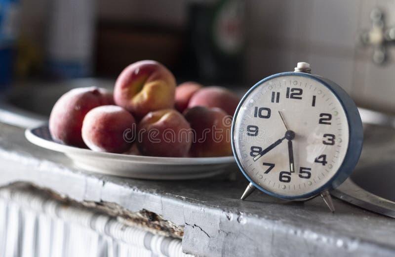 Gammal blå klocka framme av en platta av plommoner som markerar tiden för ett mellanmål royaltyfri bild