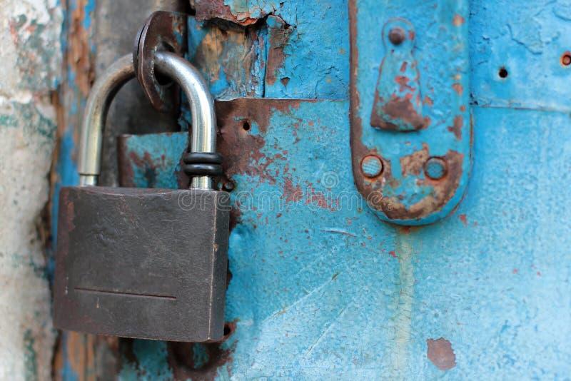 Gammal blå lantlig dörr med det rostiga låset och nyckelhålet arkivfoto