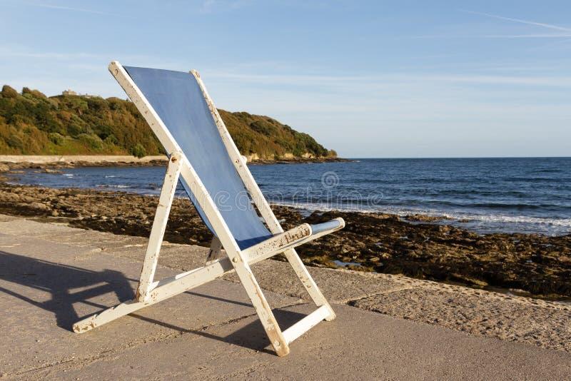 Gammal blå trädeckchair vid havet royaltyfri bild