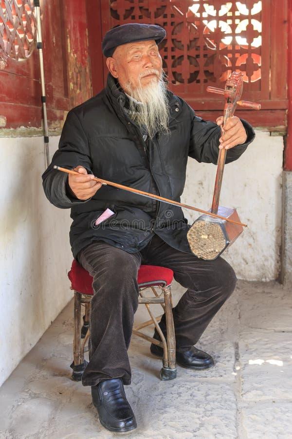 Gammal blind kinesisk man som spelar den forntida kinesiska stränginstrumenten i den ShiGu byn royaltyfria foton