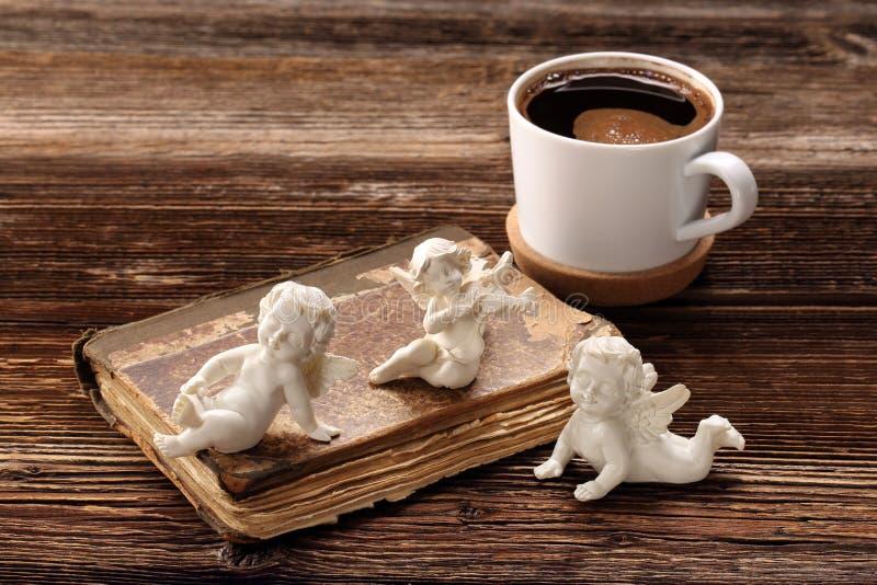 Gammal bok, de tre änglarna och kopp kaffe royaltyfria foton