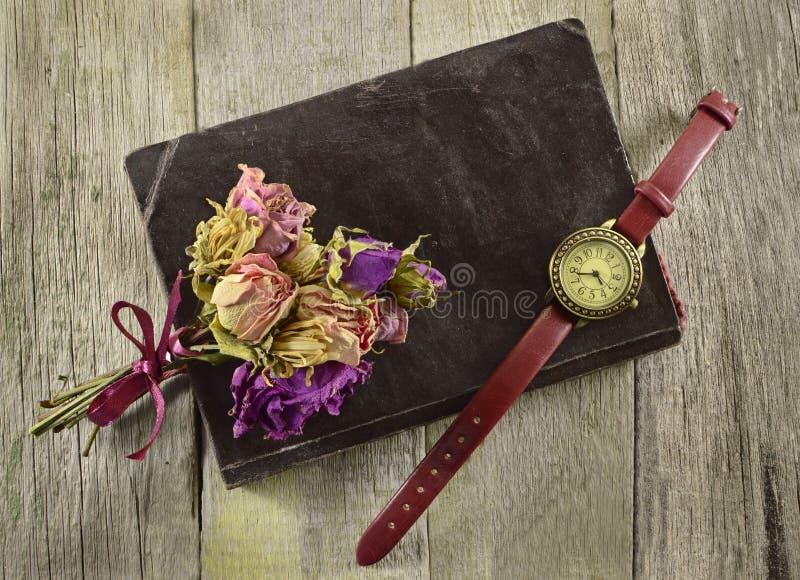 Gammal bok med klockan och blommor arkivfoto