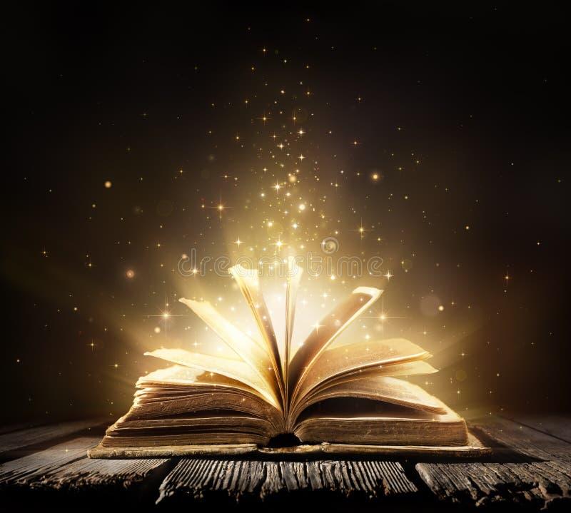 Gammal bok med magiska ljus royaltyfri foto