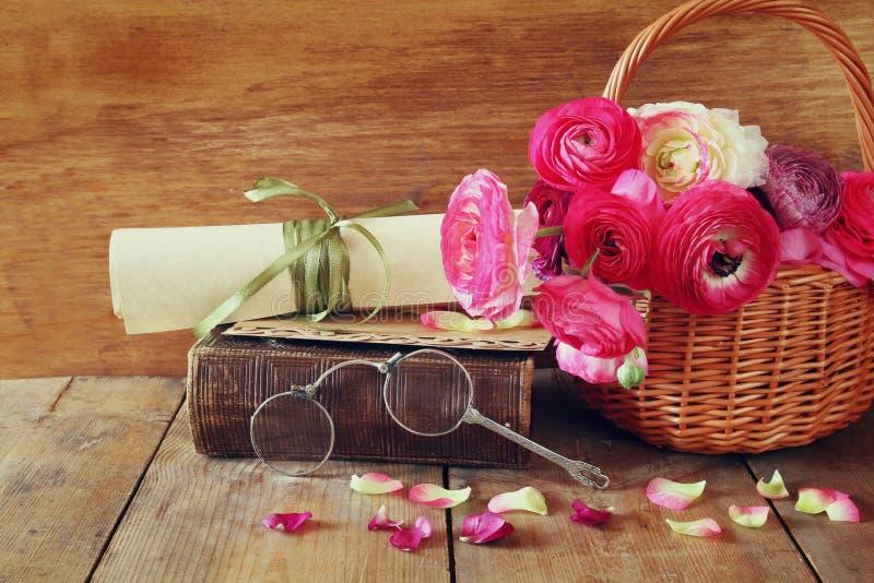Gammal bok och exponeringsglas bredvid blommor på trätabellen royaltyfri foto