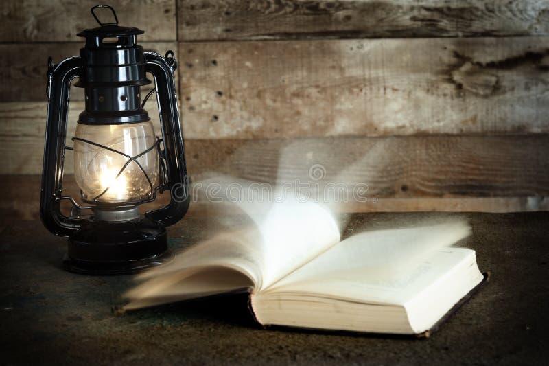 Gammal bok och fotogenlampa royaltyfria foton