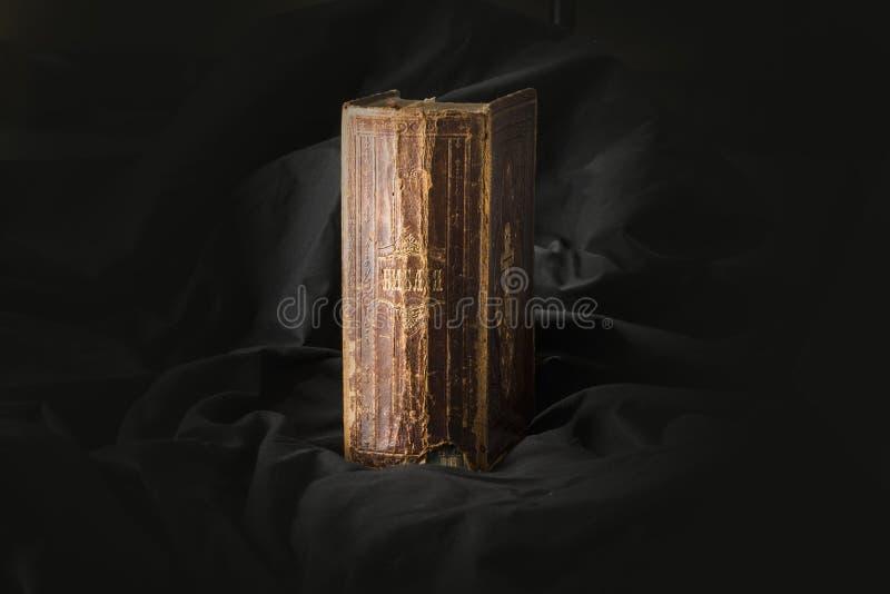 Gammal bok på svart bakgrund Forntida kristen bibel AntikvitetH arkivfoto