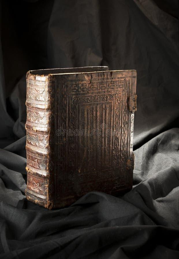 Gammal bok på svart bakgrund Forntida kristen bibel AntikvitetH arkivbild