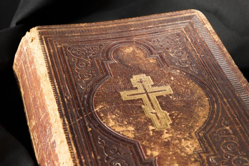 Gammal bok på svart bakgrund Forntida kristen bibel close upp royaltyfri fotografi
