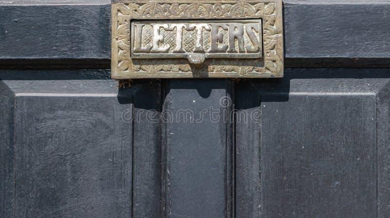 Gammal bokstavsask i dörren, traditionell väg av att leverera bokstäver till huset, gammal brevlåda arkivfoto