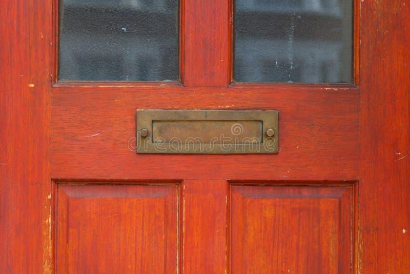 Gammal bokstavsask i dörren, traditionell väg av att leverera bokstäver till huset, gammal brevlåda royaltyfri bild