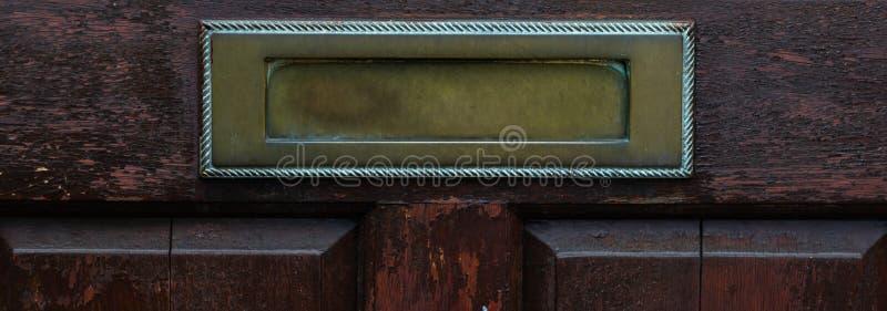 Gammal bokstavsask i dörren, traditionell väg av att leverera bokstäver till huset, gammal brevlåda fotografering för bildbyråer
