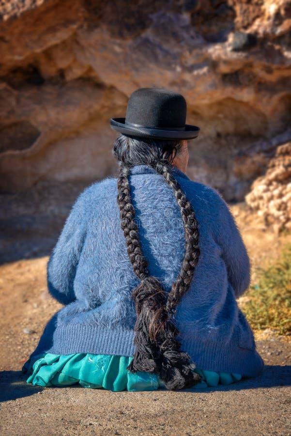 Gammal bolivian kvinna i traditionell dräkt med en hatt och långa flätade trådar arkivfoto