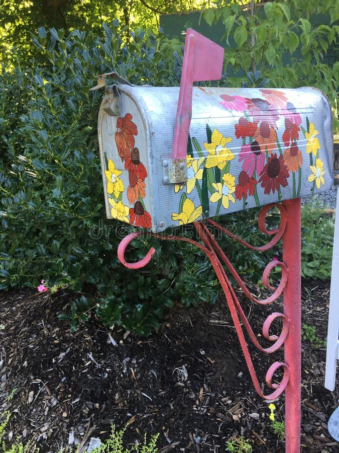 Gammal brevlåda målat nytt med blommor royaltyfri bild
