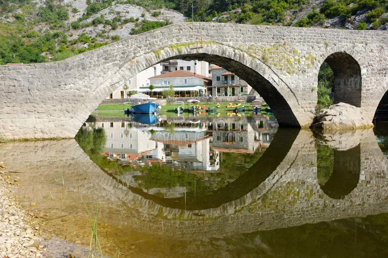 Gammal bro i den Rijeka Crnojevica byn, Montenegro royaltyfri fotografi