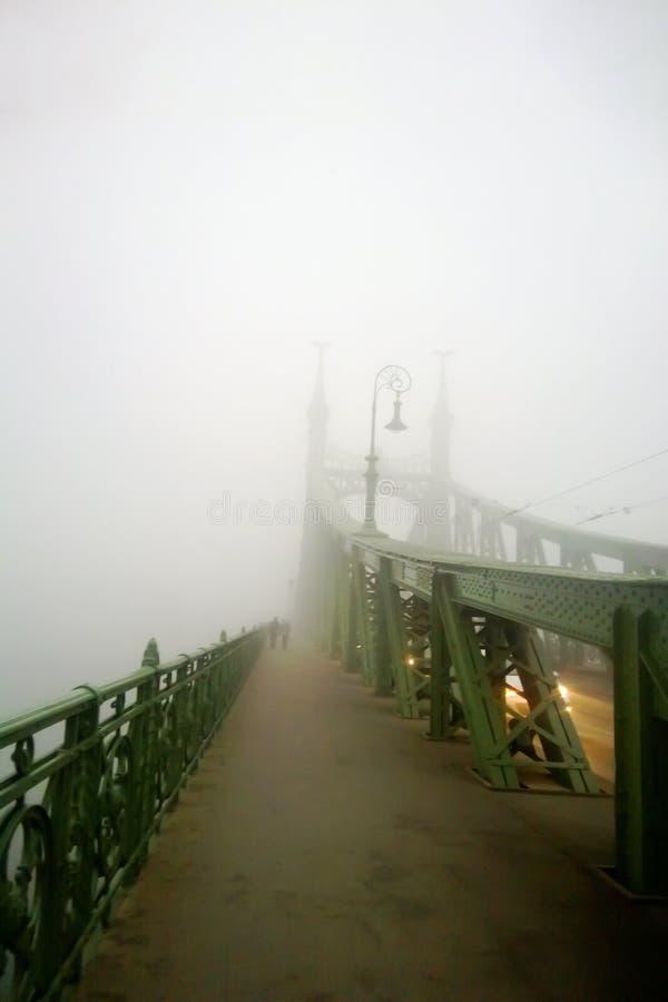gammal bro i dimman Mystisk vision Ett par av folk g?r tillsammans i dimman arkivfoto