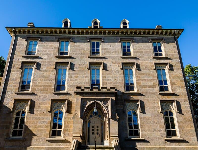Gammal brun stenbyggnad med blåa Windows royaltyfri fotografi