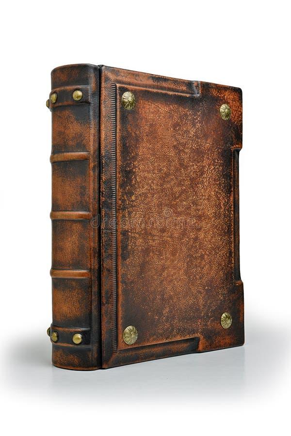 Gammal brunt piskar boken med metallben står upp till den isolerade tabellen royaltyfri foto