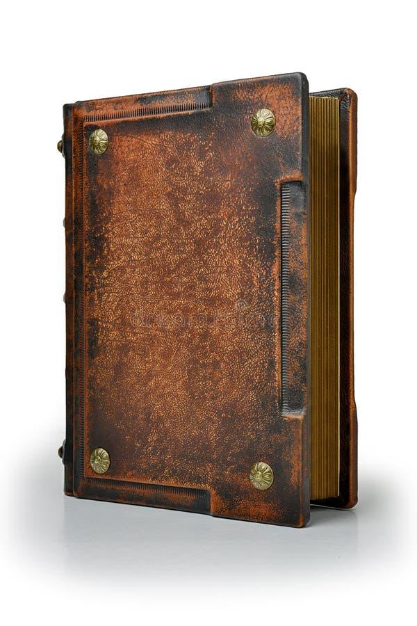 Gammal brunt piskar boken med metallben står upp till den isolerade tabellen arkivfoto