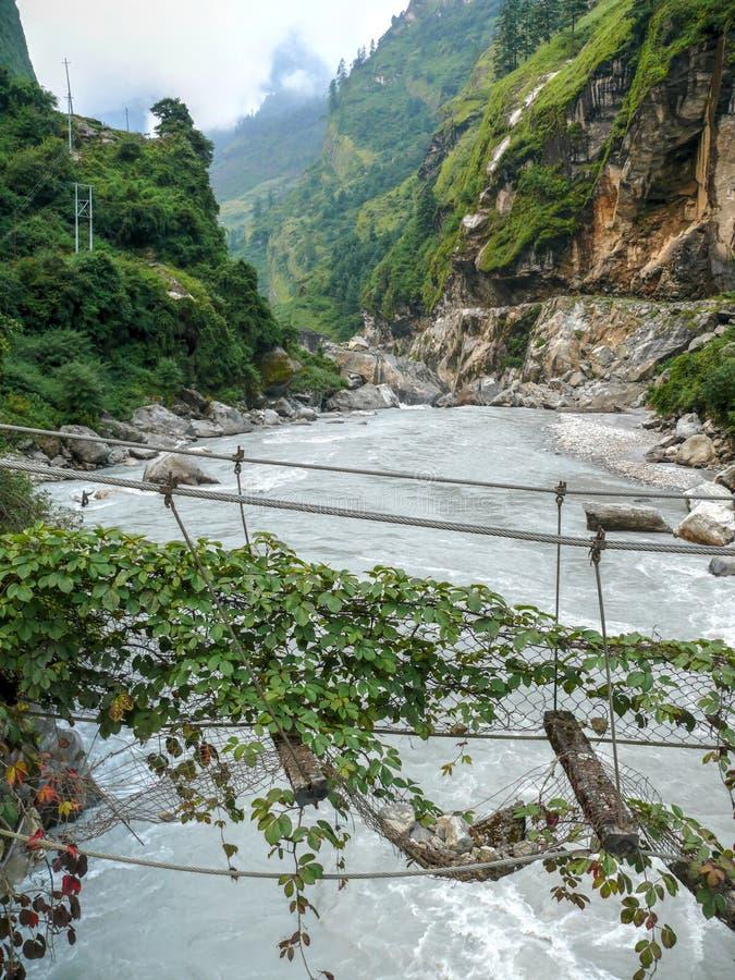 Gammal bruten bro över den Marsyangdi floden nära Dharapani - Nepal arkivbild