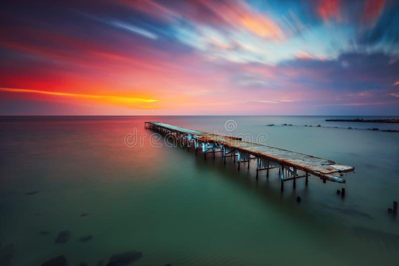 Gammal bruten bro i havet, lång exponering royaltyfri fotografi