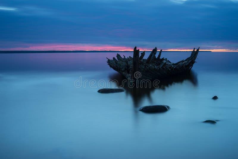 Gammal bruten fartyghaveri på kusten, ett djupfryst hav och härlig blå solnedgångbakgrund arkivfoton