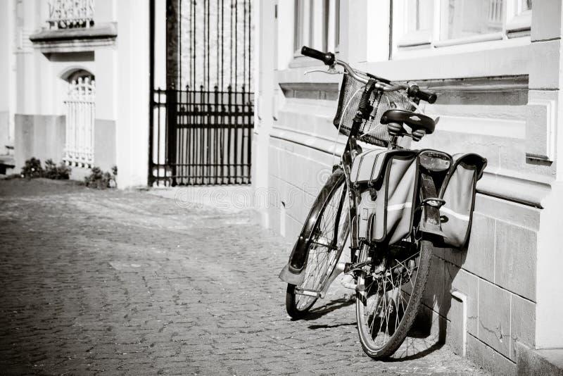Gammal bycicle som parkeras i gatan fotografering för bildbyråer