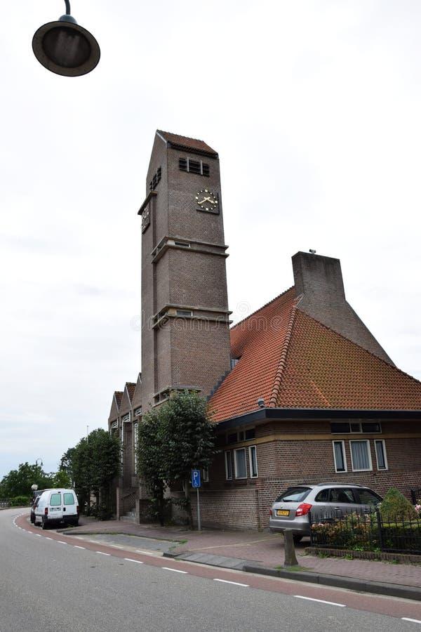 Gammal byggnad i staden nära väderkvarnen parkerar av UNESCOvärldsarvet Kinderdijk, Nederländerna arkivfoto