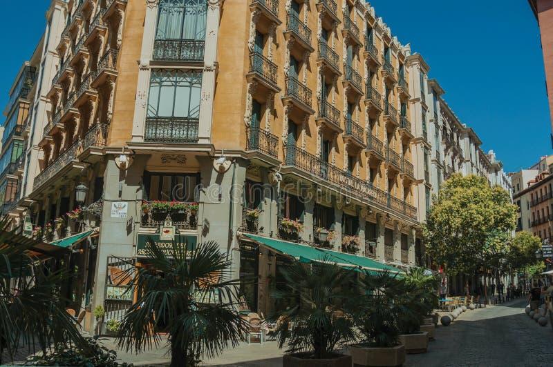 Gammal byggnad med eateryen och folk som går på en gata av Madrid fotografering för bildbyråer