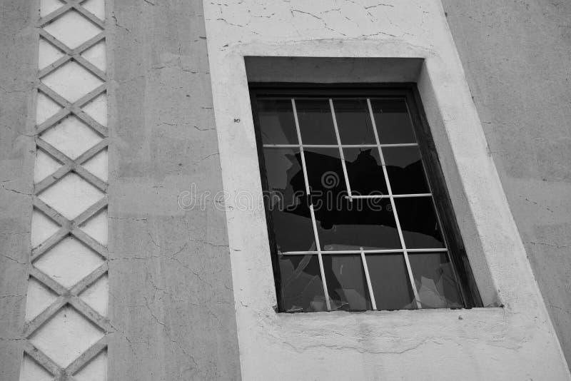 Gammal byggnad med ett brutet fönsterexponeringsglas och en bandmodell arkivbilder