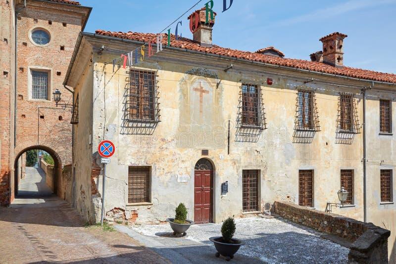 Gammal byggnad med freskomålningen med korset i en solig sommardag, blå himmel i Mondovi, Italien royaltyfria foton