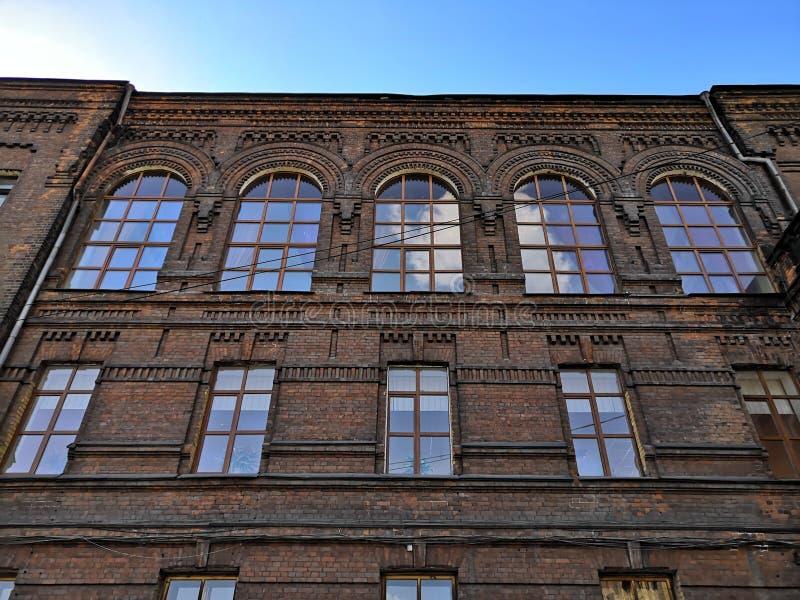Gammal byggnad med stora Windows, röd tegelsten arkivfoto