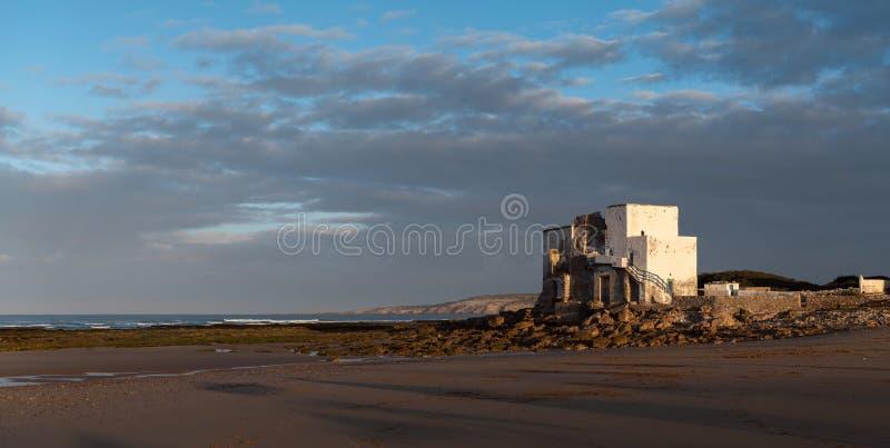 Gammal byggnad på kusten av Sidi Kaouki, Marocko, Afrika skjuten solnedgångtid för exponering long Marockos fantastiskt brännings royaltyfria bilder