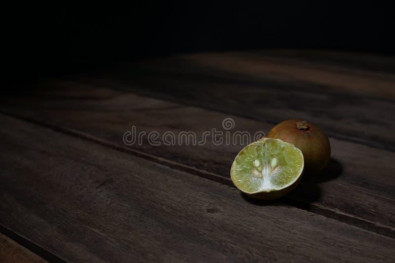Gammal citronskiva på tappningen trätabell royaltyfri foto