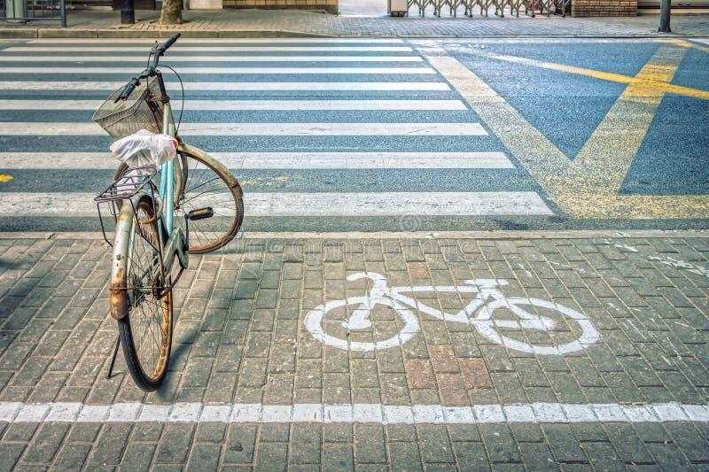 Gammal cykel med symbol på cykelparkeringsplats på vägrenen royaltyfria bilder
