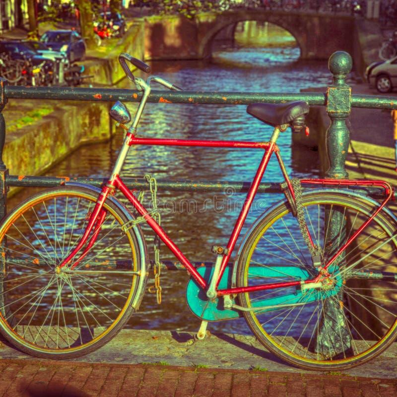 Gammal cykel på kanalbron i Amsterdam arkivbild